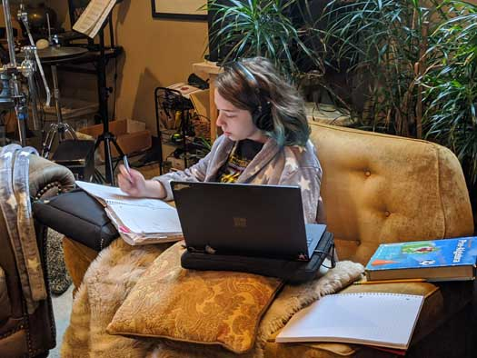 A Middle School student writes in a notebook, with her laptop beside her, in a living room.