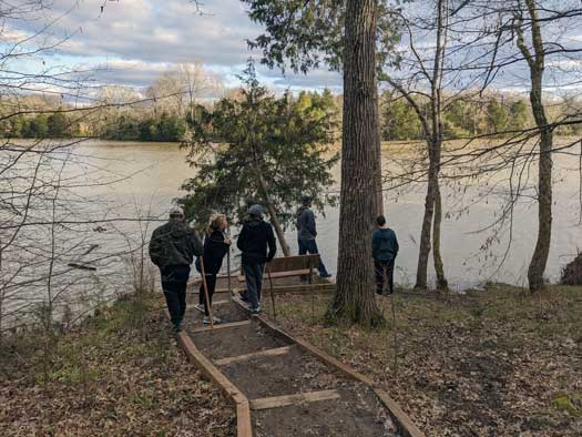 A family walks down to a river, on a trail.