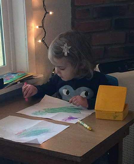 A toddler studies at a table.