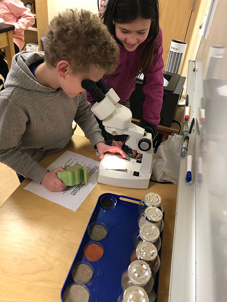 Elementary students examine sand under a microscope.