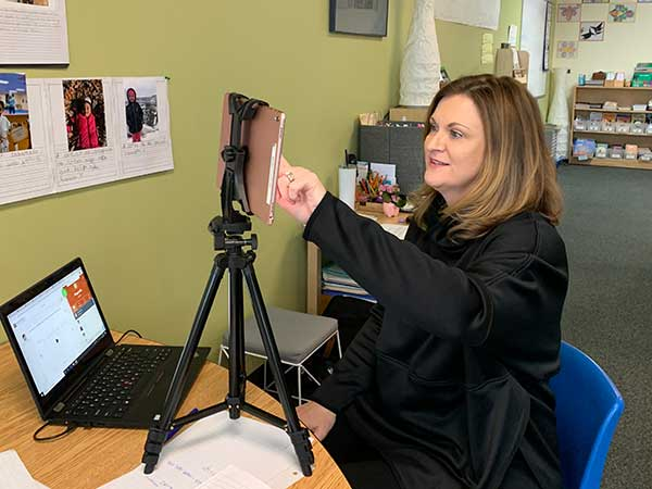A teacher presses the screen on a tripod-mounted tablet computer