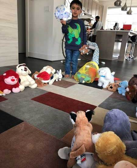 A boy has his stuffed animals arranged in a circle