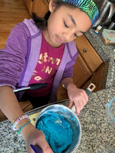 An elementary girl stirs a thick blue substance in a sauce pan.