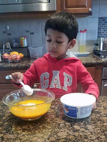 A toddler adds ingredients to a bowl