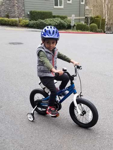 A toddler rides his bike with training wheels