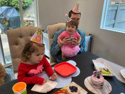 A toddler looks at her birthday cake with her family