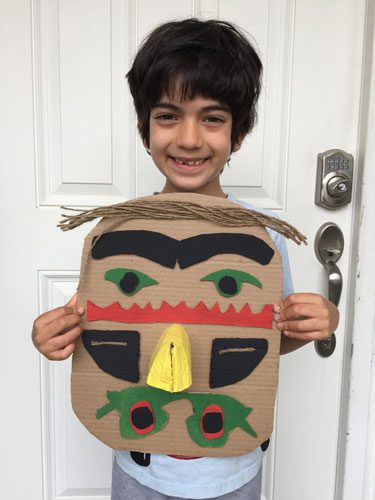An elementary boy holds  up the Nothwest Coastal art-influenced mask he made