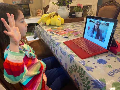 A preschool student interacts with her teacher via a laptop screen