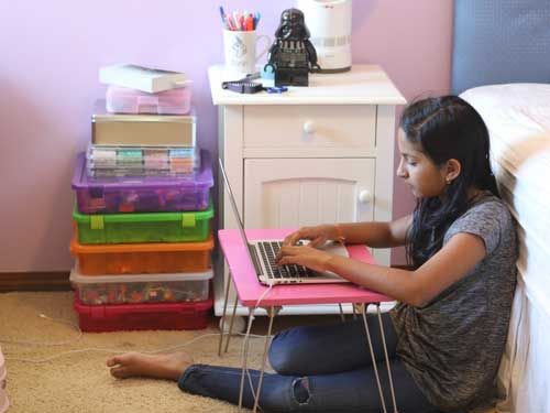 A student types on her laptop