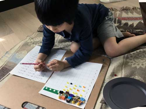 A student uses the bead board and Lego pieces to practice division facts