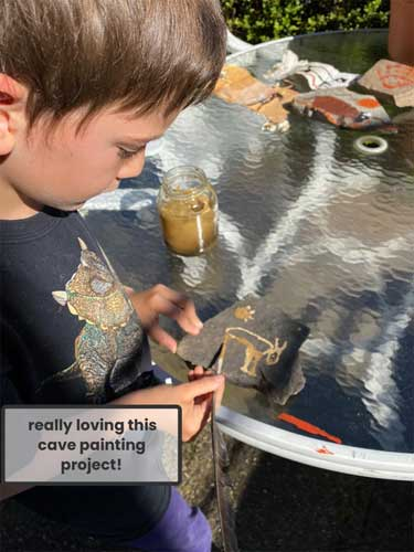 A student creates his version of cave painting