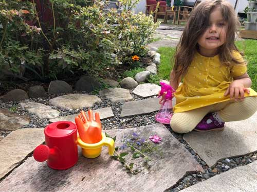 A girl sits beside a row of rainbow-colored items-red watering can, orange glove, yellow pitcher and flowers