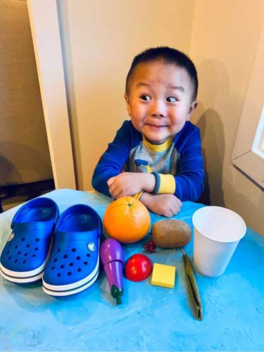 A boy smiles excitedly at a table with rainbow-colored items, blue clog, purple toy, red item and more