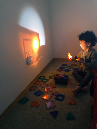 A toddler reflects gold light on the wall with a gold filter