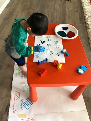 A toddler paints using various items as stamps