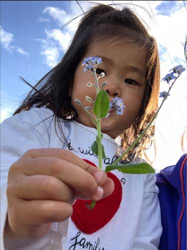 A toddler holds up a sprig of Forget Me Nots