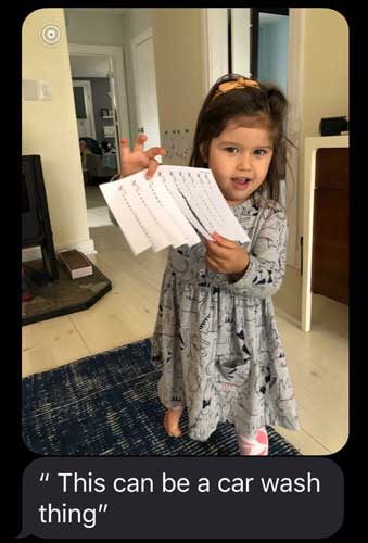 A preschool student holds up a piece of paper that she has cut into almost separate strips: This can be a car wash thing