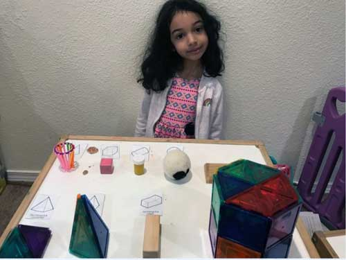 A preschool girl sits at a table where she has been identifying different shapes.