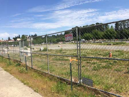A vacant lot behind a chain link fence.