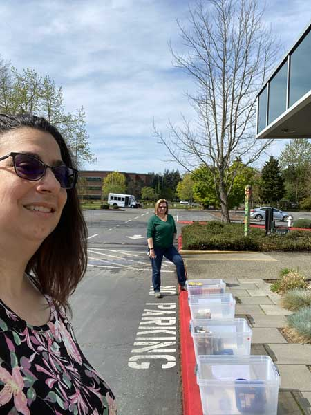 Two women stand by empty plastic bins on a sidewalk.