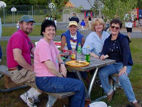 Five adults sit at a picnic table smiling