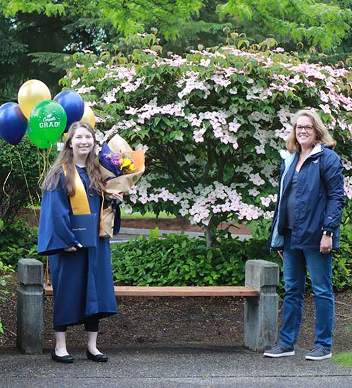 A grad in gown, with diploma, flowers and balloons, smiles a few feet away from an older woman