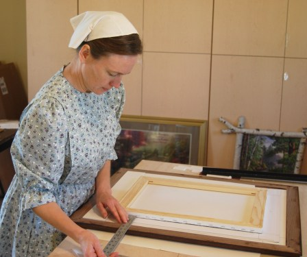 The whole Bardwell family is involved in their framing business. Karla's doing framing in Frameworxz's Studio.