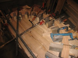 Ferdinand glues up thin strips of wood into a curved arch on a curved molding jig, then runs it through his Woodmaster.