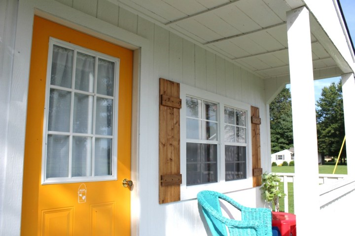 Shutters hung on each side of she shed front window
