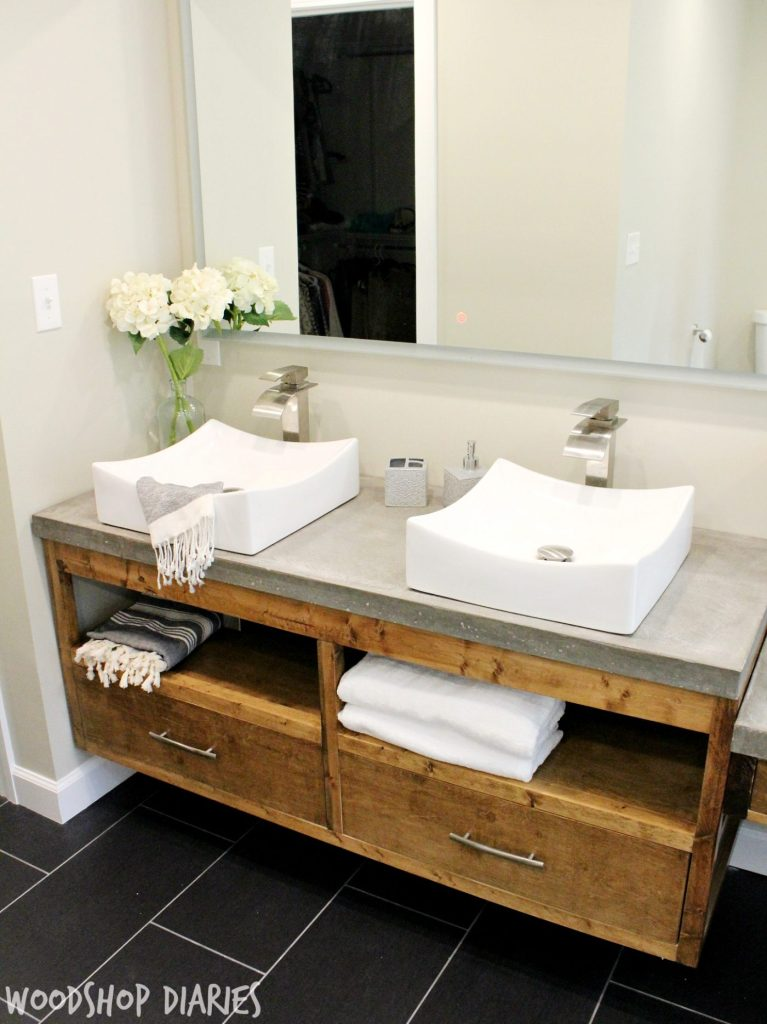 Modern Bathroom with DIY Floating vanity and concrete counter tops, vessel sinks, and silver finishes. Gorgeous modern style bathroom