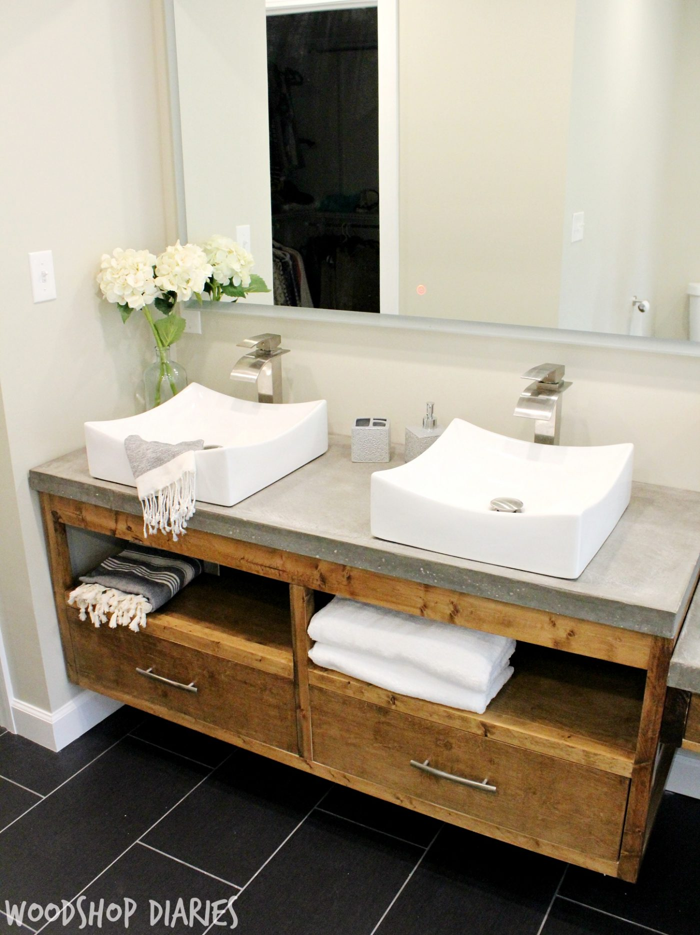Modern bathroom with diy floating vanity and concrete counter tops vessel sinks and silver