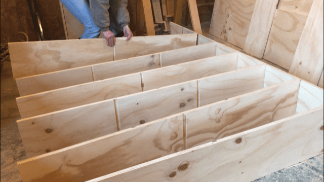 Placing shelves into dadoes to assemble modern DIY boookshelf