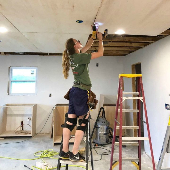 Shara screwing plywood panels into trusses on ceiling of garage apartment