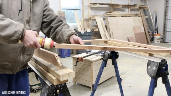 Applying wood glue to mitered joints on picture frame made with dowels