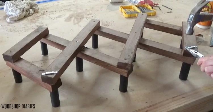 Hammer wall hanger hardware into DIY Accordion Coat Rack