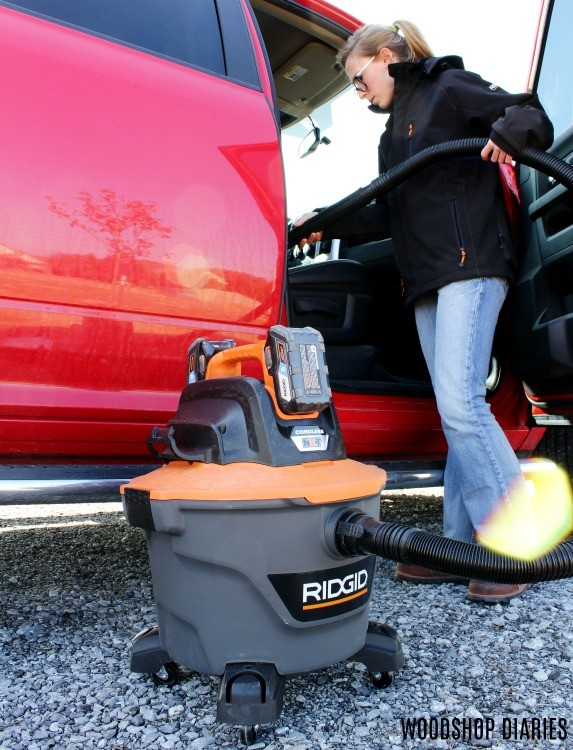 Shara Woodshop Diaries vacuuming truck in Ridgid heated jacket