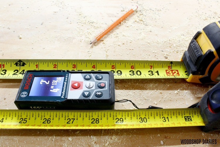 Close up of Bosch Blaze Laser Distance Measurer compared to tape measure readings