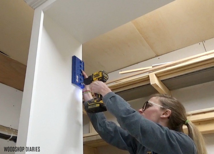 Drill shelf pin holes into DIY entertainment center cabinet