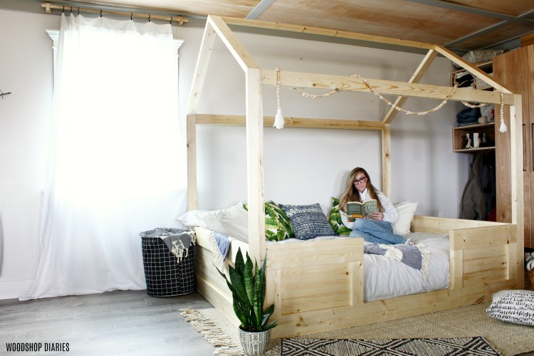 Shara Woodshop Diaries hanging out in a fun DIY kids house bed reading a book