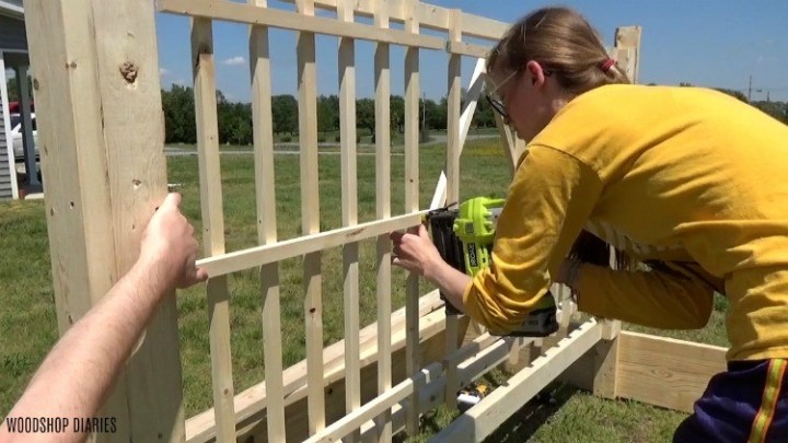 Nailing pieces of garden bed trellis in place with a nail gun