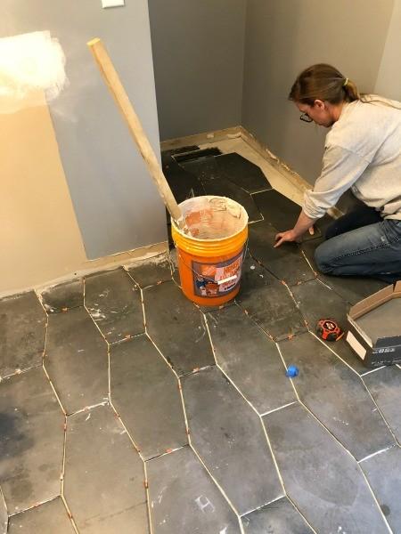 Shara tiling master bathroom floor into back corner