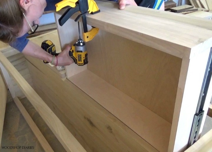 Shara screwing drawer fronts onto drawer boxes from inside