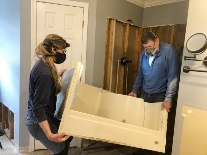 Shara and Dad carrying out old shower stall in pieces