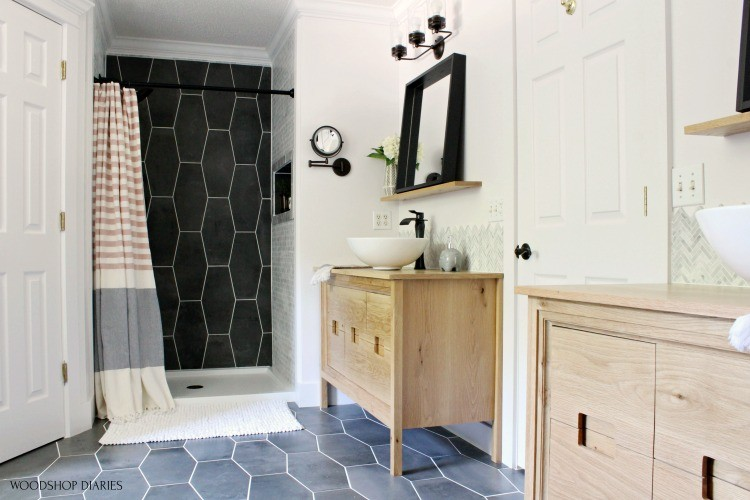 Wide view of master bathroom white oak double vanities, black mirrors, and two tone shower nook