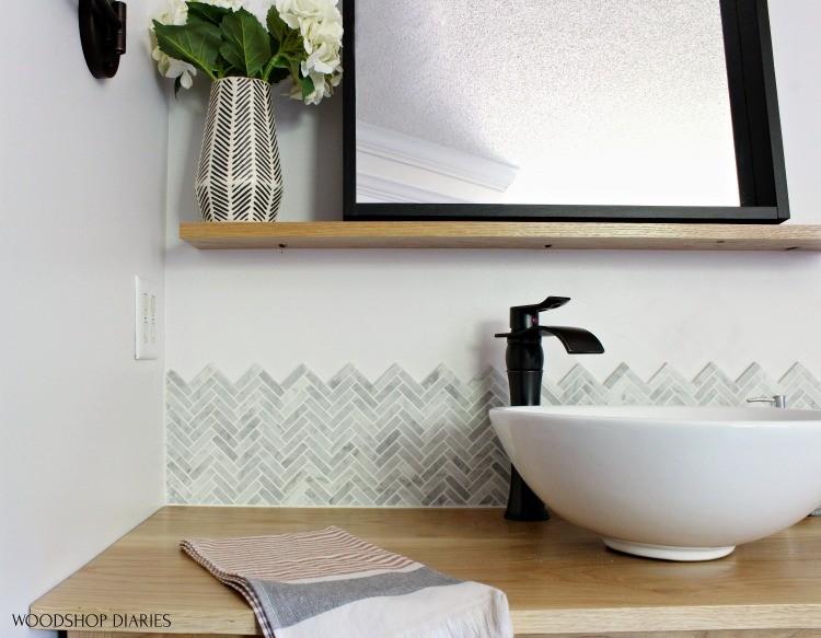 Close up of Jet Stream backsplash tile over top of white oak vanity with black framed mirror on floating shelf