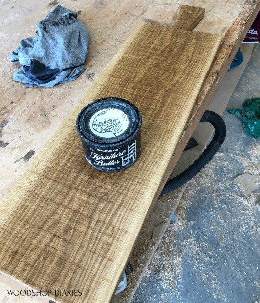 Can of furniture butter sitting on finished serving board with rough saw marks