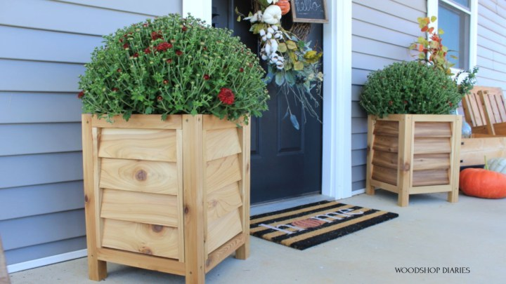 DIY Louvered Cedar Planters on each side of black front door with red mums