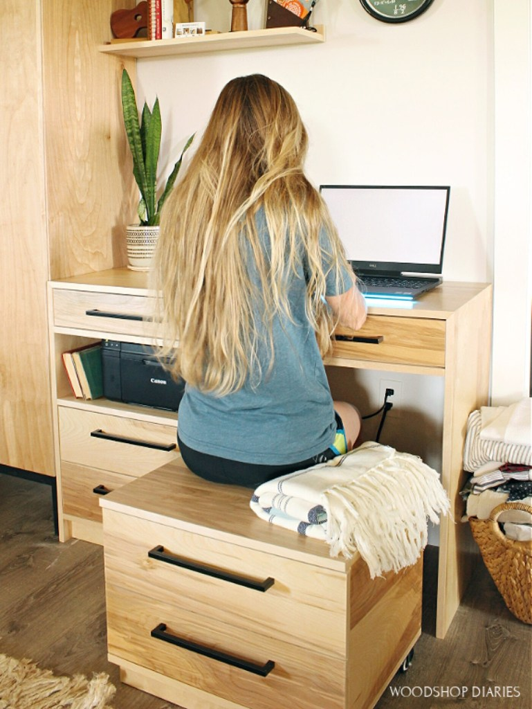 Shara Woodshop Diaries sitting at DIY dresser desk with storage seat pulled out
