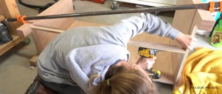 Installing bottom panel trim piece into cabinet