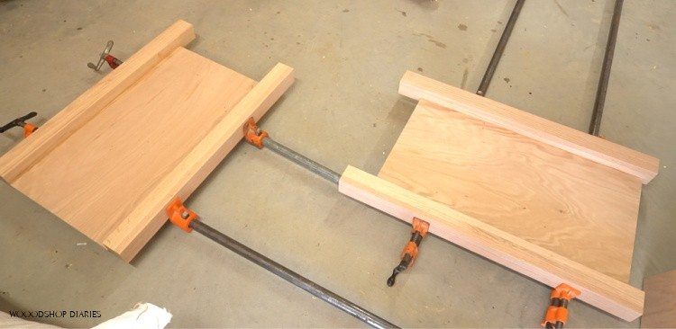 Two L shaped desk side panels glued up in clamps